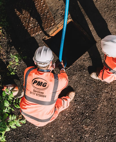 Men PMG Services with pipe in drain